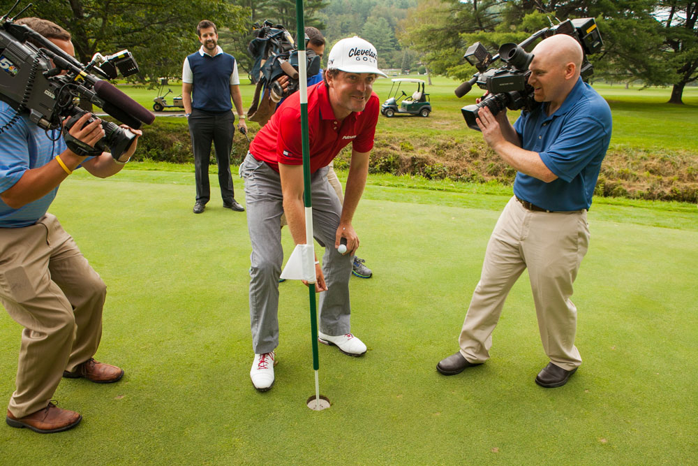 Keegan Bradley smiles for the camera as he pickes up his ball